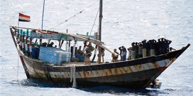 Feb. 16: In this image made available by the Ministry of Defence in London, a naval boarding party from HMS Cornwall guard Somali pirates after their dhow was boarded in the Indian Ocean.