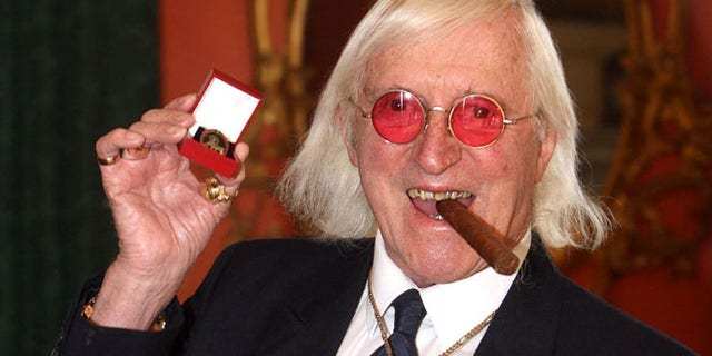 March 25, 2008: This file photo shows Jimmy Savile showing a medal in London.