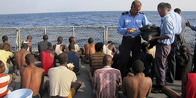 March 13: In this photo released by the Government of India Press Information Bureau, Indian naval officers distribute food to the captured pirates aboard an Indian naval ship in the Arabian Sea, off the coast of Kochi, India.