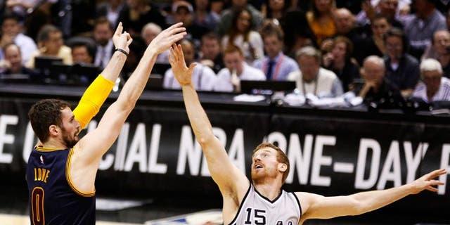 Mar 12, 2015; San Antonio, TX, USA; Cleveland Cavaliers forward Kevin Love (0) shoots the ball over San Antonio Spurs power forward Matt Bonner (15) during the first half at AT&T Center. Mandatory Credit: Soobum Im-USA TODAY Sports