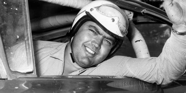 Junior Johnson looks out his car window before a race in 1959. (RacingOne/Getty Images)