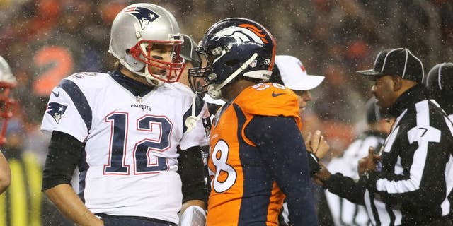 New England Patriots quarterback Tom Brady (12) and Denver Broncos outside linebacker Von Miller (58) have words during the first half at Sports Authority Field at Mile High. Mandatory Credit: