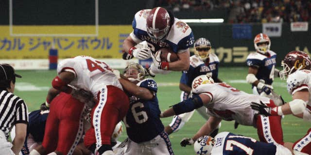 FILE - In this Jan. 12, 1992 file photo, East's Kevin Turner, of Alabama, dives over the top for a touchdown in the fourth quarter of the Japan Bowl, the American collegiate all-star football game, at the Tokyo Dome.