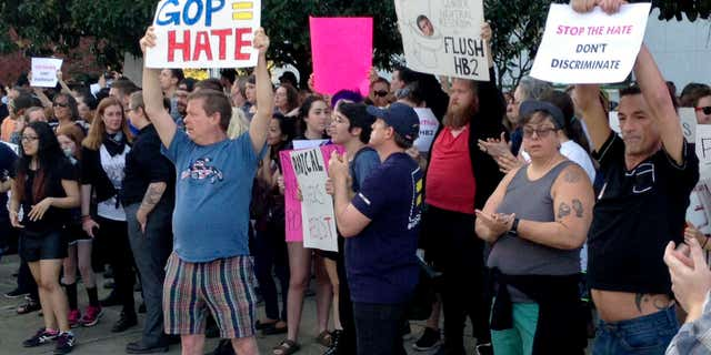 People protest outside the North Carolina Executive Mansion in Raleigh, N.C., Thursday, March 24, 2016. North Carolina legislators decided to rein in local governments by approving a bill Wednesday that prevents cities and counties from passing their own anti-discrimination rules.