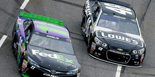 MARTINSVILLE, VA - NOVEMBER 01: Denny Hamlin, driver of the #11 FedEx Ground Toyota, races Jimmie Johnson, driver of the #48 KOBALT TOOLS Chevrolet, during the NASCAR Sprint Cup Series Goody's Headache Relief Shot 500 at Martinsville Speedway on November 1, 2015 in Martinsville, Virginia. (Photo by Jeff Zelevansky/Getty Images)