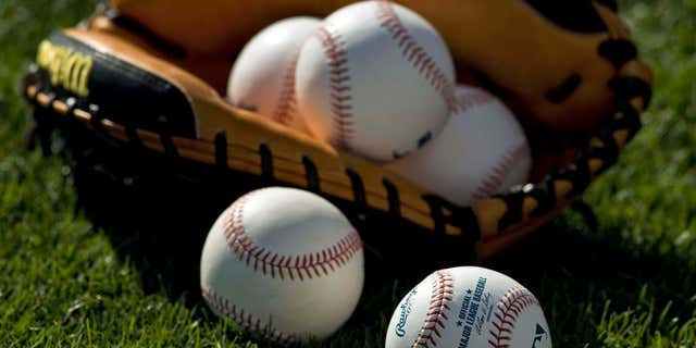 March 25, 2013: Baseballs and a catcher's mitt lie on the grass before a MLB spring training baseball game between the Boston Red Sox and Baltimore Orioles in Sarasota, Florida.