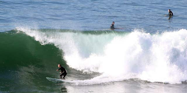 FILE - In this Tuesday, Dec. 8, 2015, file photo, surfers ride a wave at Lunada Bay in Palos Verdes Estates, Calif.