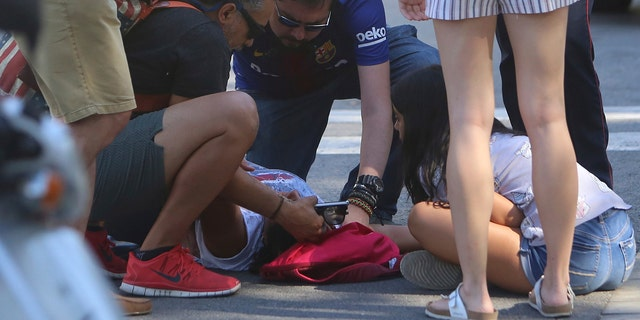 An injured person is treated in Barcelona, Spain, Thursday, Aug. 17, 2017 after a white van jumped the sidewalk in the historic Las Ramblas district, crashing into a summer crowd of residents and tourists and injuring several people, police said. (AP Photo/Oriol Duran)
