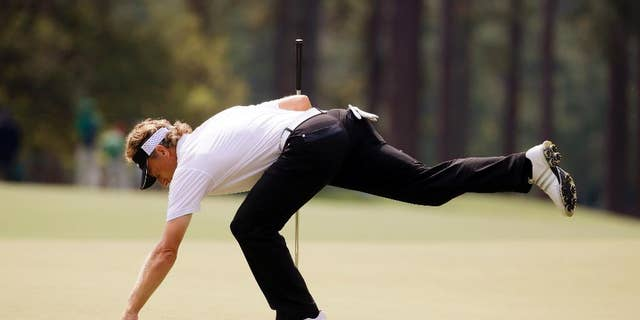 Bernhard Langer, of Germany, gets his ball out of the cup after putting on the eighth green during the second round of the Masters golf tournament Friday, April 11, 2014, in Augusta, Ga. (AP Photo/Darron Cummings)