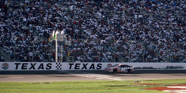 FORT WORTH, TX April 6, 1997: Jeff Burton takes the checkered flag to win the Interstate Batteries 500, the first NASCAR Cup race to be held at the new Texas Motor Speedway. (Photo by ISC Images & Archives via Getty Images)
