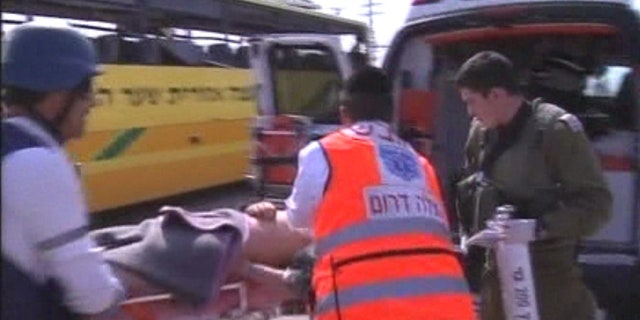 April 7: An injured person is loaded into an ambulance after a Palestinian mortar strikes an Israeli bus.