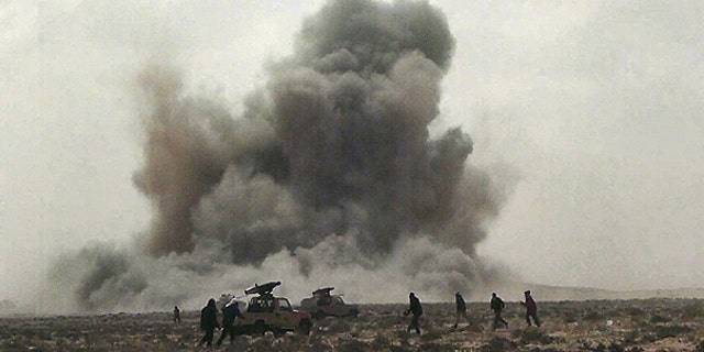 FILE: In this April 7, 2011, image made from television, a dust cloud is seen following the explosion of a missile, outside the strategic oil port of Brega, Libya.