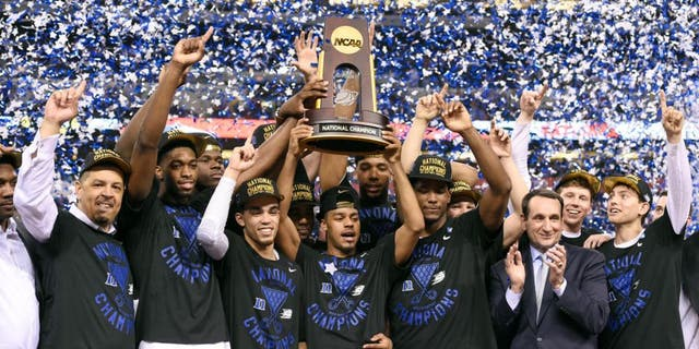 Apr 6, 2015; Indianapolis, IN, USA; Duke Blue Devils celebrate with the NCAA trophy on the podium after defeating the Wisconsin Badgers 68-63 in the 2015 NCAA Men's Division I Championship game at Lucas Oil Stadium. Mandatory Credit: Robert Deutsch-USA TODAY Sports