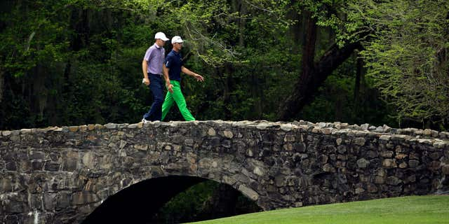 April 10, 2015: Jordan Spieth, left, walks over the Nelson Bridge with Billy Horschel during the second round of the Masters golf tournament.