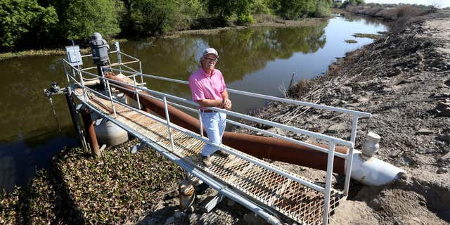 March 27, 2015: Farmer Rudy Mussi poses at one of his pumps that draws water from a slough to irrigate his farm land in the Sacramento-San Joaquin Delta near Stockton, Calif.