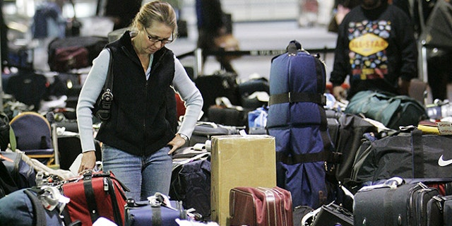 In this Feb. 20, 2007 file photo, Carolann Manfredi, of Princeton, N.J., searches through luggage for a bag she says has been missing for five days, at the Philadelphia International Airport. AP