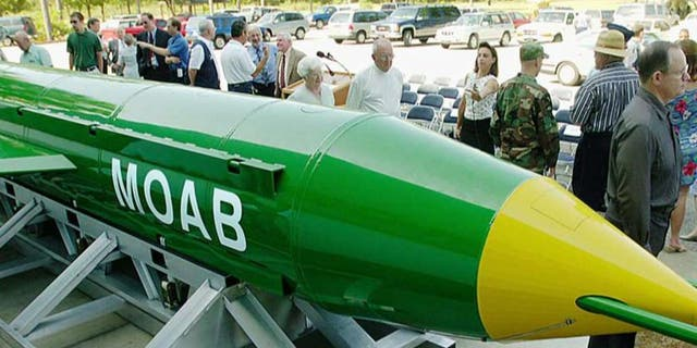 In this May 2004 photo, a group gathers around a GBU-43B, or massive ordnance air blast (MOAB) weapon, on display at the Air Force Armament Museum on Eglin Air Force Base near Valparaiso, Fla.