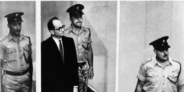 """1962: Adolf Eichmann stands in his glass cage, flanked by guards, in the Jerusalem courtroom where he was tried for war crimes committed during World War II. The basics of Adolf Eichmann's story are well-documented. He was commonly known as the """"architect of the Holocaust"""" for his role in coordinating the Nazis' policy of genocide. He fled Germany only to be captured in Argentina by the Mossad, taken to Israel for trial, and hanged."""