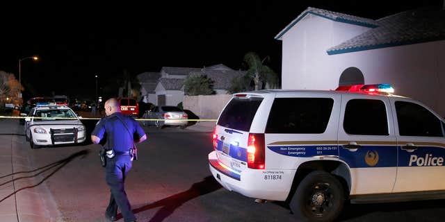 April 16, 2015: A Phoenix Police officer walks in front of the blocked off street near a home where authorities say five people were killed inside after a shooting.