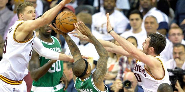 Apr 19, 2015; Cleveland, OH, USA; Boston Celtics guard Isaiah Thomas (4) drives between Cleveland Cavaliers center Timofey Mozgov (20) and forward Kevin Love (0) in the third quarter in game one of the first round of the NBA Playoffs at Quicken Loans Arena. Mandatory Credit: David Richard-USA TODAY Sports