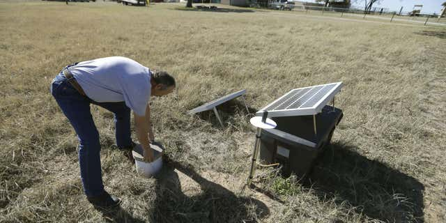 Nov. 19, 2014: In this file photo, Scott Passmore, director of public works, checks on a solar powered seismic monitor installed by Southern Methodist University that records earthquakes in the area around Reno, Texas.