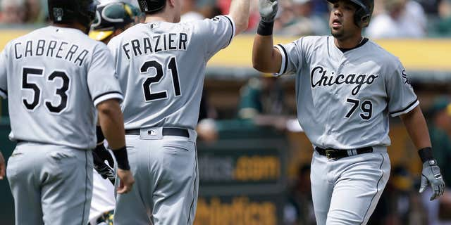 FILE - In this Thursday, April 7, 2016 file photo, Chicago White Sox's Jose Abreu, right, is congratulated by Todd Frazier (21) and Melky Cabrera (53) after hitting a two run home run off Oakland Athletics' Kendall Graveman in the sixth inning of a baseball game in Oakland, Calif.