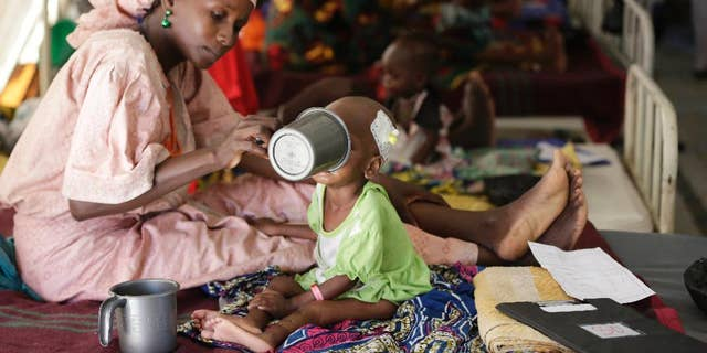 FILE - In this Monday Aug. 29, 2016 file photo, a mother feeds her malnourished child at a feeding centre run by Doctors Without Borders in Maiduguri Nigeria. During its seven-year uprising, Boko Haram extremists have killed more than 20,000 people and displaced more than 2.6 million in Nigeria and neighboring Cameroon, Niger and Chad. ( AP Photo/Sunday Alamba, File)