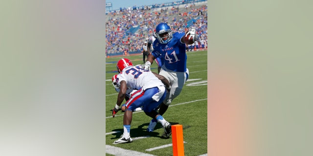 FILE - In this Sept. 21, 2013, file photo, Kansas tight end Jimmay Mundine (41) slips past Louisiana Tech defensive back Xavier Woods (39) for a touchdown during the second half of an NCAA college football game in Lawrence, Kan.  Just about the only bright spot in the Kansas pass attack this season has been the guy who was perhaps the least expected to make a contribution: tight end Jimmay Mundine. He's also the only guy catching touchdown passes. (AP Photo/Orlin Wagner, File)