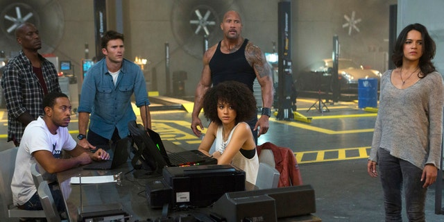 "Chris ""Ludacris"" Bridges, seated left, and Nathalie Emmanuel, seated right, and Tyrese Gibson, standing from left, Scott Eastwood, Dwayne Johnson and Michelle Rodriguez in ""The Fate of the Furious."""