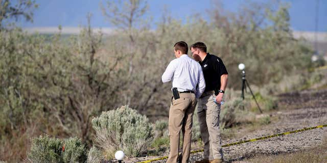 April 30, 2015: Officers with the Department of Public Safety State Bureau of Investigation process the scene where human remains inside a suitcase were discovered on the side of I-80 near Saltair in Magna, Utah.