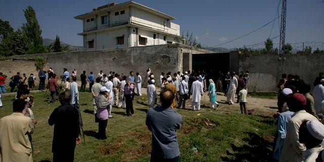 May 3: Local people and media gather outside the perimeter wall and sealed gate into the compound and a house where Al Qaeda leader Usama bin Laden was caught and killed late Monday, in Abbottabad, Pakistan.