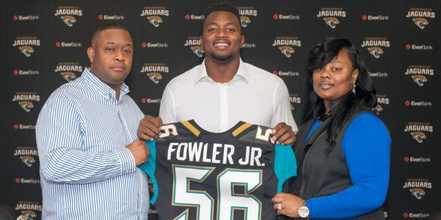 Dante Fowler, cener, the Jacksonville Jaguars first round draft pick, holds up his jersey as he stands between his parents Dante Fowler, Sr. and Lenora Fowler during an NFL football press conference at EverBank Field in Jacksonville, Fla., Saturday May 2, 2015. (Fran Ruchalski/The Florida Times-Union via AP)