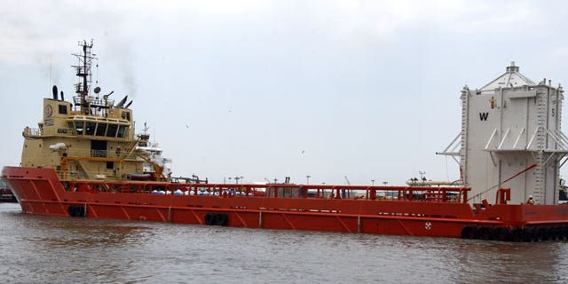 The barge Joe Griffin turns around in a channel after a crane loaded a chamber, right, that will be used to help contain oil leaking from the Deepwater Horizon oil drilling platform, in Port Fourchon, La.