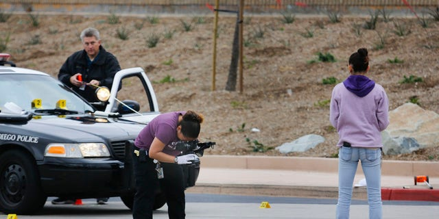 Members of the San Diego Police Department collect evidence at the scene of a fatal police officer involved shooting of a 15-year-old boy in one of the parking lots in front of Torrey Pines High School, early Saturday morning.