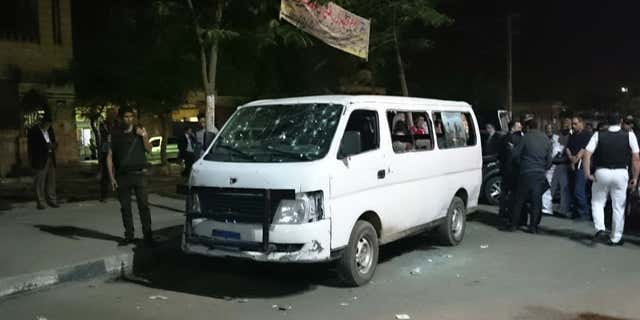 May 8, 2016: Egyptian police and civilians gather around a bullet ridden microbus in the south Cairo neighborhood of Helwan.