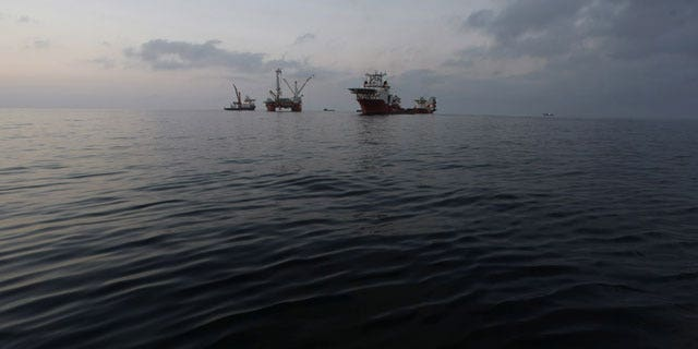 May 7: The Q4000, center, which has lowered the oil containment vessel to the sea floor, is seen at sunset from the offshore supply vessel Joe Griffin, at the site of the Deepwater Horizon oil spill containment efforts in the Gulf of Mexico off the coast of Lousiana.