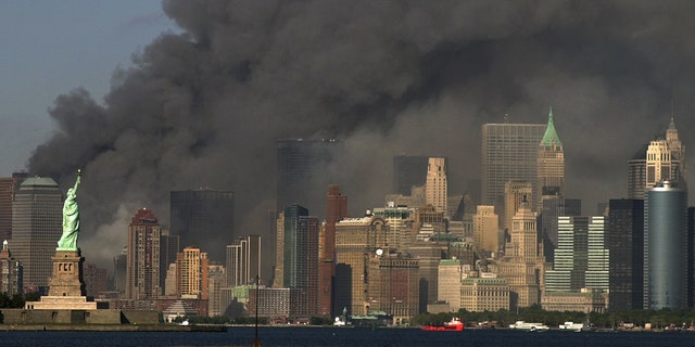 FILE -- In this Sept. 11, 2001 file photo, thick smoke billows into the sky from the area behind the Statue of Liberty, lower left, where the World Trade Center towers stood.