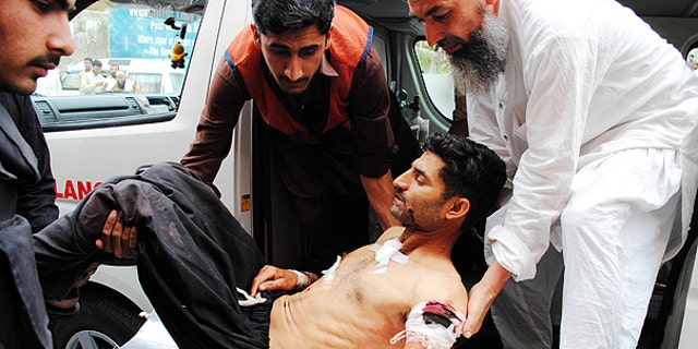 May 13:  In this photo released by China's Xinhua News Agency, people transfer an injured man to a hospital in Peshawar, Pakistan.