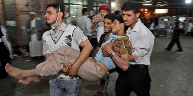 May 11: Anti-government protestors carry a wounded demonstrator to a field hospital during clashes with Yemeni security forces in Sanaa, Yemen.