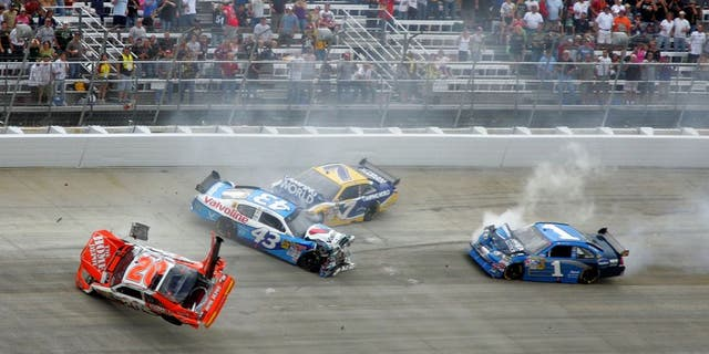DOVER, DE - SEPTEMBER 27: (L-R) Joey Logano, driver of the #20 Home Depot Toyota, flips his car after he was involved in a wreck with Reed Sorenson, driver of the #43 Valvoline Dodge, Robby Gordon, driver of the #7 Camping World Toyota and Martin Truex Jr., driver of the #1 Vaseline MEN Body Lotion Chevrolet during the NASCAR Sprint Cup Series AAA 400 at Dover International Speedway on September 27, 2009 in Dover, Delaware. (Photo by Jerry Markland/Getty Images for NASCAR)