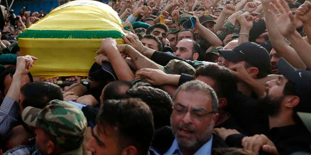 May 13, 2016: Hezbollah supporters carry the coffin of their slain commander Mustafa Badreddine, draped in a Hezbollah flag, during his funeral procession in a southern suburb of Beirut, Lebanon.