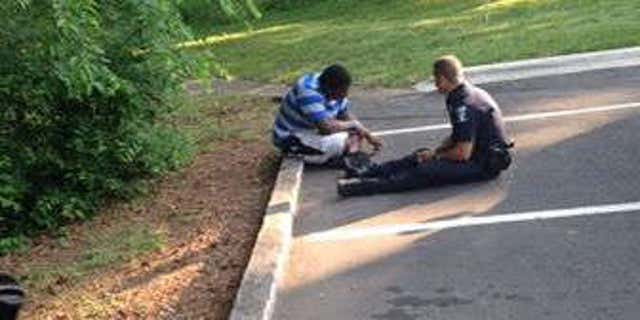 Photo shows Officer Tim Purdy talking with autistic high school student.