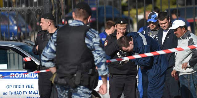 May 14, 2016: Police investigators work on the site of a brawl at the Khovanskoye cemetery in in Moscow, Russia.