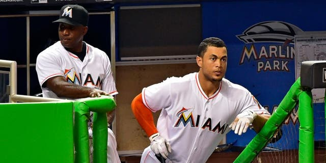 Apr 18, 2016; Miami, FL, USA; Miami Marlins hitting coach Barry Bonds (left) talks with Marlins right fielder Giancarlo Stanton (right) at the steps of the dugout during the second inning of a game against the Washington Nationals at Marlins Park. Mandatory Credit: Steve Mitchell-USA TODAY Sports