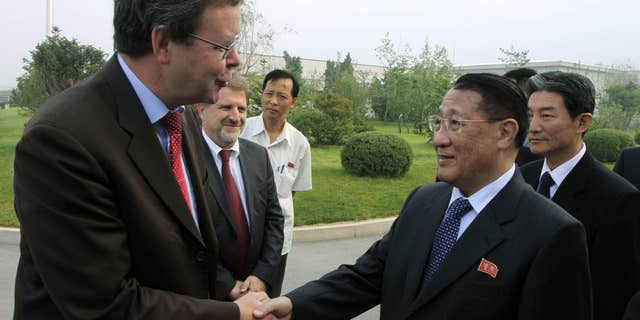 FILE - In this Sept. 6, 2014 file photo, North Korea's Kang Sok Ju, right, a member of the Political Bureau of the Central Committee of the Workers' Party of Korea (WPK) and secretary of the WPK, shakes hands with German Ambassador to North Korea Thomas Schaefer as he leaves Pyongyang Airport in Pyongyang, North Korea to visit Germany, Belgium, Switzerland, Italy and Mongolia.