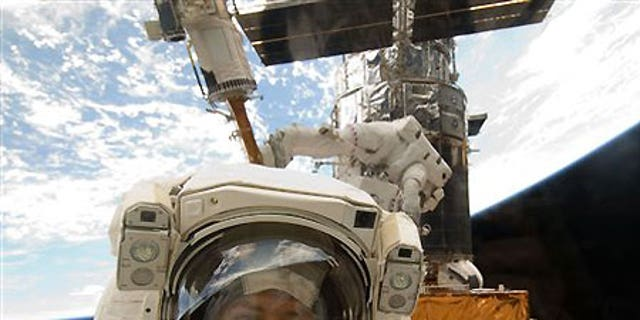 Astronaut Mike Massimino is photographed through a window of the Space Shuttle Atlantis - file photo.