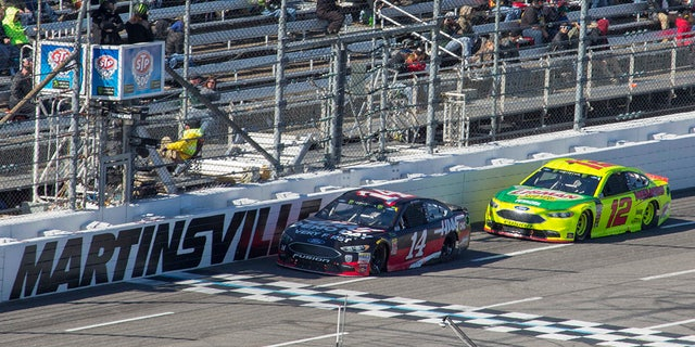 Clint Bowyer (14) passes Ryan Blaney (12) for the lead during a NASCAR Cup Series auto race at Martinsville Speedway in Martinsville, Va., Monday, March 26, 2018. (AP Photo/Matt Bell)