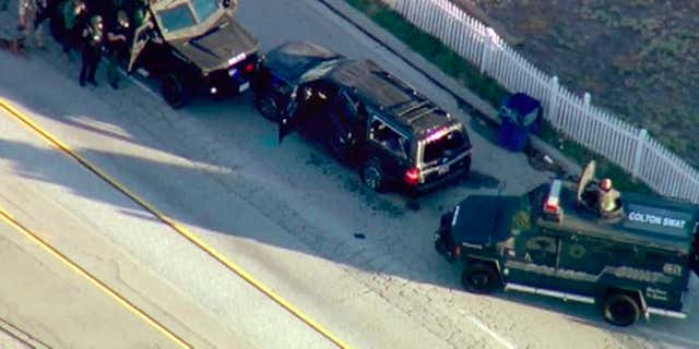 FILE - In this Dec. 2, 2015, file image, taken from video, armored vehicles surround an SUV following a shootout in San Bernardino, Calif.