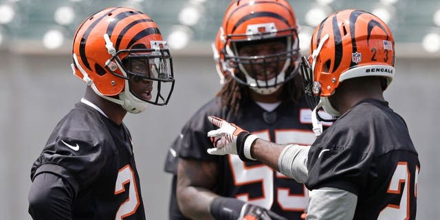 Cincinnati Bengals first round draft pick Darqueze Dennard, a cornerback from Michigan State, left, gets instructions from veteran cornerback Terence Newman, right, during an NFL football organized team activity, Tuesday, May 27, 2014, in Cincinnati. (AP Photo/Al Behrman)