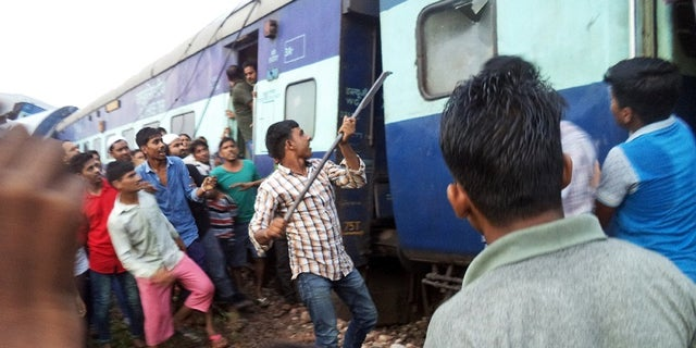 A volunteer breaks the glass of a train compartment window to rescue passengers trapped after an accident near Khatauli, in the northern Indian state of Uttar Pradesh, Saturday, Aug. 19, 2017. Six coaches of a passenger train derailed in northern India on Saturday, killing more than 20 people and injuring dozens, officials said. (AP Photo)